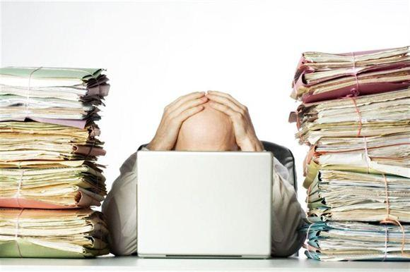 man holding his head in front of a computer surrounded by stacks of paper
